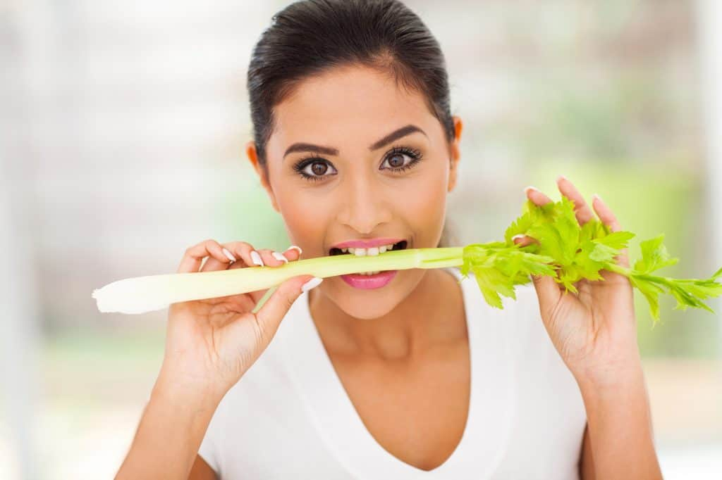 girl biting a celery stick and wondering if her cat can eat it
